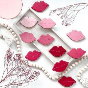 Lukrowane ciasteczka w formie czerwonych ust ułożone razem z dekoracją